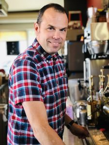 Copper Star Coffee owner Bill Sandweg works the espresso machine with a smile on his face.