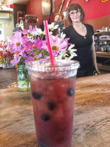 Barista Erika, in the background, next to the iced tea drink she created. Earl Grey and Passion Plum teas with a shot of lavender, finished off with a few blueberries.
