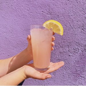 Picture of hands holding a glass of lavender lemonade with a lemon slice on the edge of the glass.