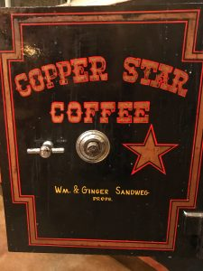 The door of a black safe is painted with Copper Star Coffee and Wm. and Ginger Sandweg Proprieters
