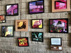 Numerous colorful photographs of the Melrose District on a wall at Copper Star Coffee.