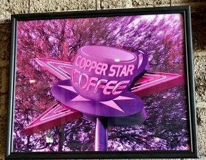Colorful photograph of the Copper Star Coffee sign by September Artist of the Month.