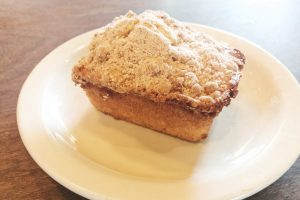 Coffee cake loaf with cinnamon crumb topping on a plate.