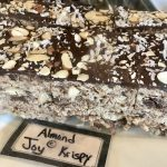 Cut squares of Almond Joy Rice Krispie Treats covered with a layer of chocolate and almonds.