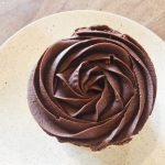 Chocolate cupcake with swirled chocolate frosting on a white plate.